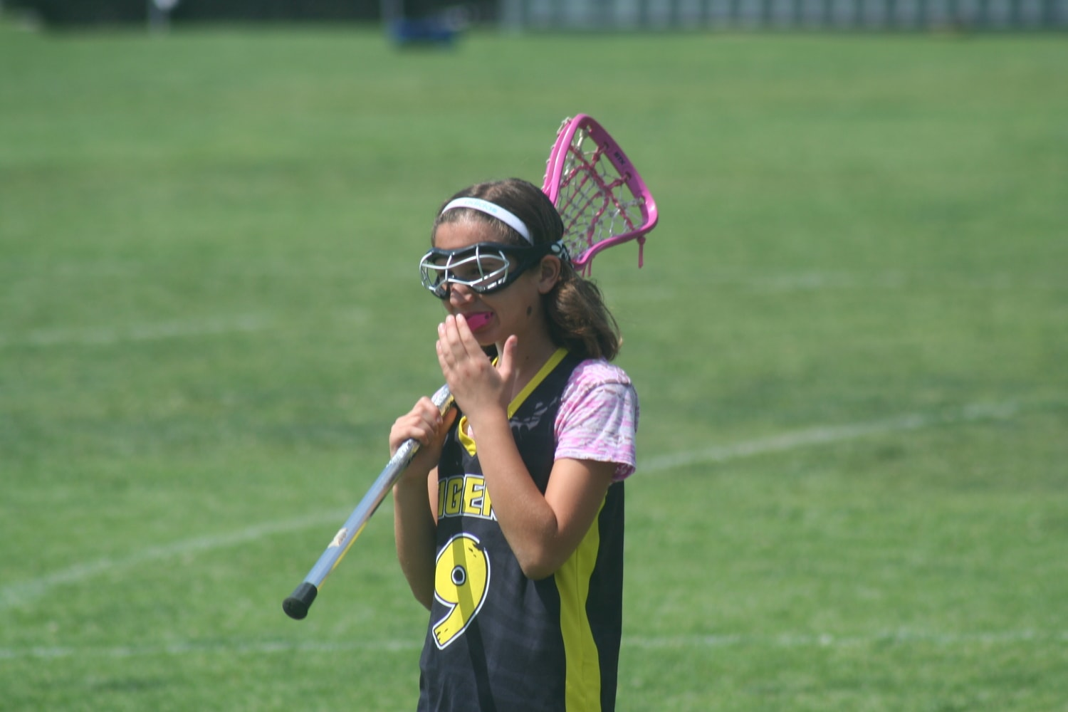 Sports Injuries: A young lacrosse player has proper eye protection and mouthguard in place