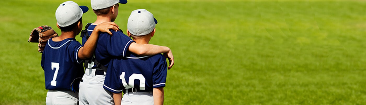 Young baseball players grouped together after a game waiting for healthy post-game snacks