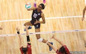 volleyball player spiking ball past two opponents