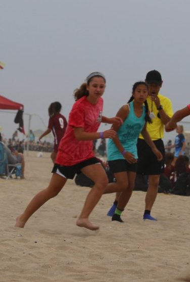 Supplements: Young girls playing sand soccer at the beach